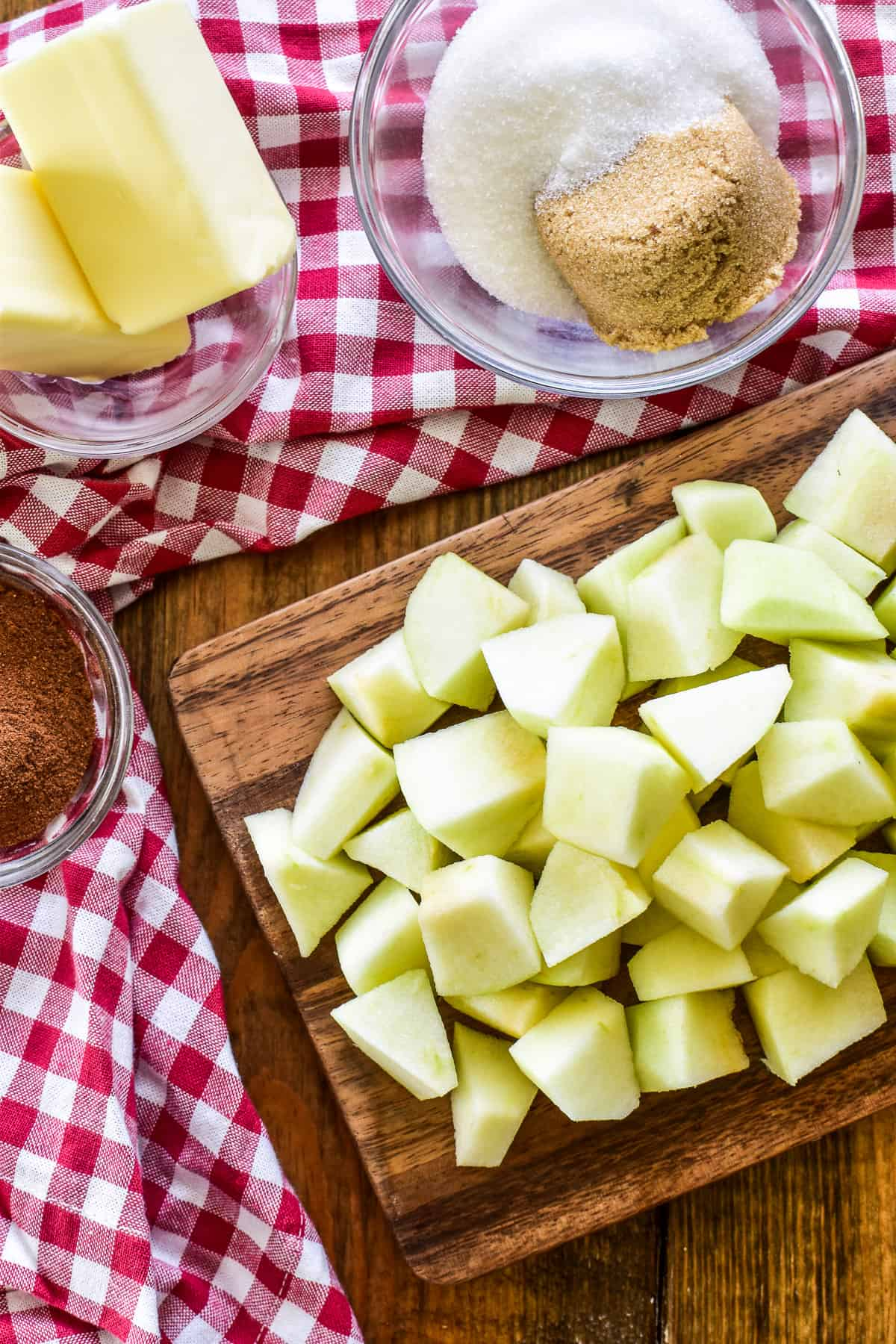 Chopped apples on a cutting board with other ingredients to make fried apples
