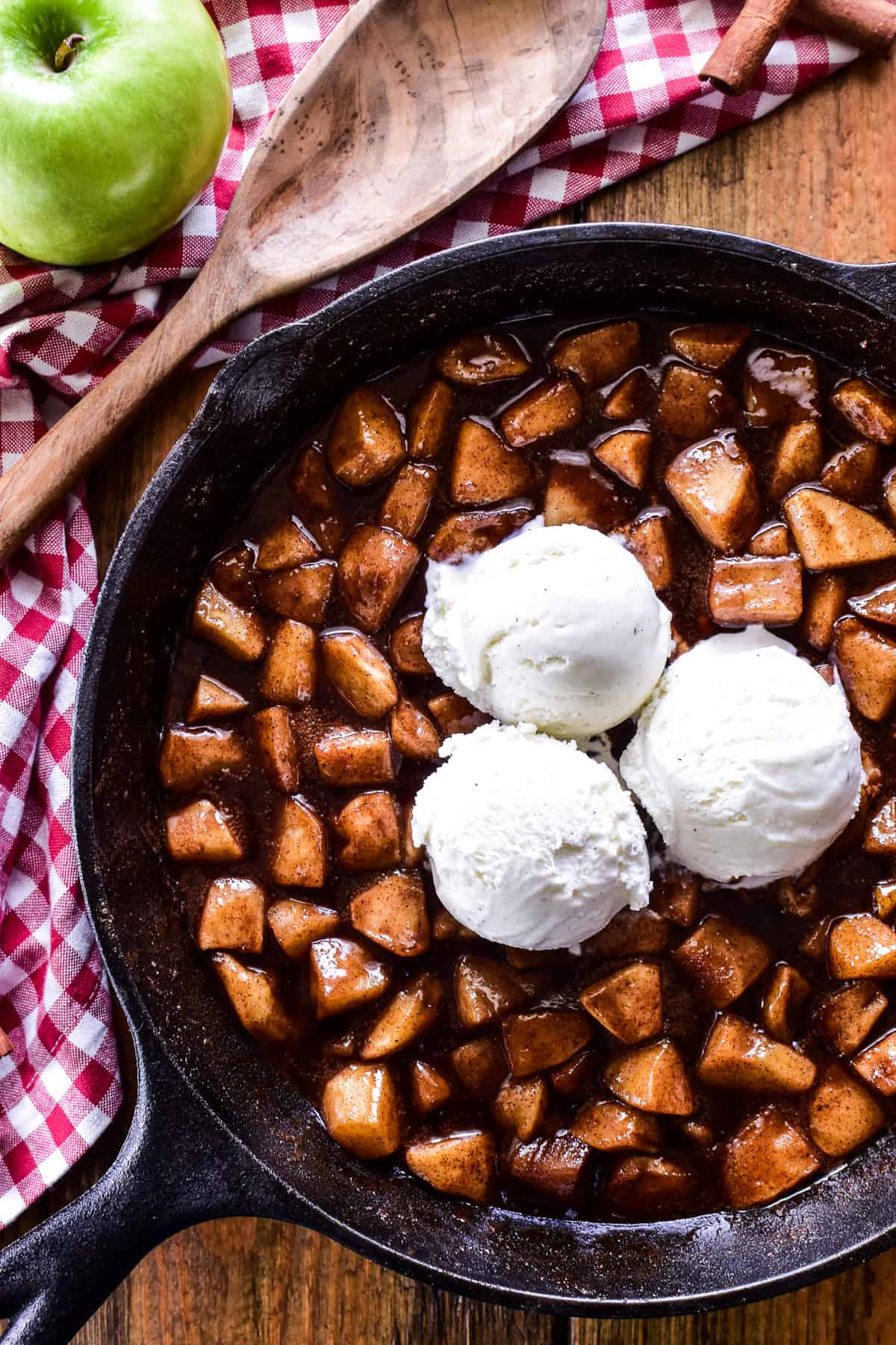 Fried Apples in a cast iron skillet with 3 scoops of vanilla ice cream and a wooden serving spoon